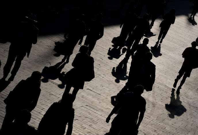 Workers are seen walking along the Southbank during the morning rush-hour in London, Britain